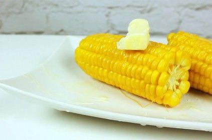 Biały talerz z kukurydzą i masłem stojący na białym stole