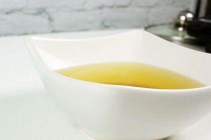 Biała miska z rosołem stojąca na białym stole