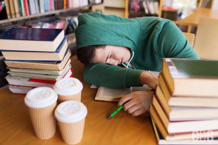 Student obłożony książkami śpi na biurku