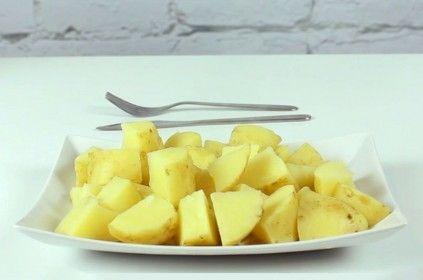Biały talerz z ziemniakami stojący na białym stole
