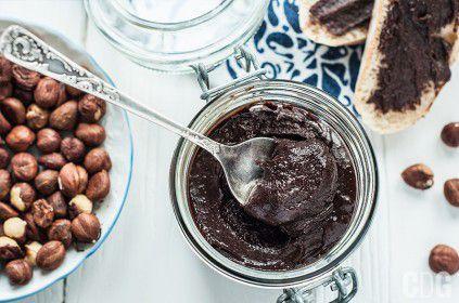 Nutella w słoiczku z łyżeczką, orzechy laskowe na talerzu, dwie kromki posmarowane