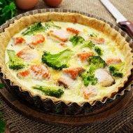 Tarta z łososiem i brokułami w foremce na desce. obok leżą cebule, nóż i natka pietruszki