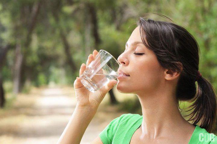 Kobieta w zielonym pijąca wodę ze szklanki