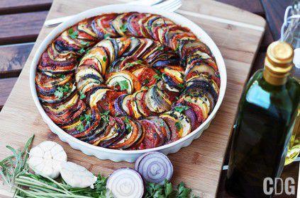 Ratatuj upieczone w formie na tartę, leży na desce do krojenia obok pietruszki i czosnku oraz butelki oliwy