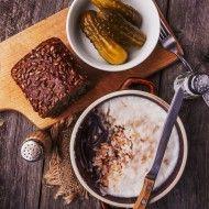 Smalec z dziczyzny w kamionce z nożem, obok deska z ciemnym chlebem i miska z ogórkami kiszonymi