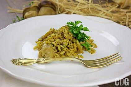 risotto z borowikami udekorowane zieloną pietruszką podane na talerzy ze złotym widelcem