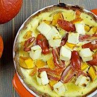 Tarta gryczana z dynią, serem i pomidorkami na stole z dwiema dyniami