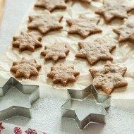 kruche ciasteczka wykrojone na stole, ułożone na pergaminie