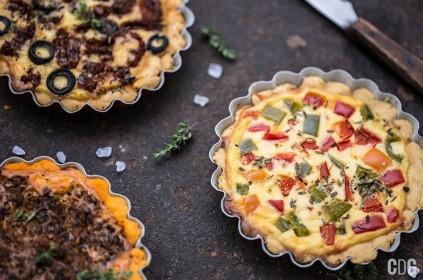Mini pizze w trzech odsłonach na blacie z gruboziarnistą solą i ziołami