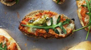 bruschetta ze świeżym pesto z bazylii oraz pulpą pomidorową ozdobiona listkiem rukoli