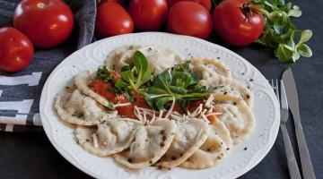 Ravioli ułożone na talerzu dookoła, w środku polane sosem pomidorowym, na ciemnym blacie, w tle świeże pomidory