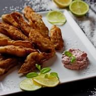 Paluszki rybne w tempurze, ozdobione limonką i podane z dipem.