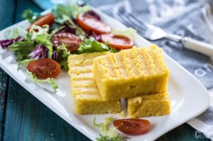 3 kawałki polenty kukurydzianej na talerzu z sałatką