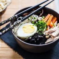 Zupa Ramen w miseczce z jajkiem, makaronem, marchewką, mięsem, grzybami i glonami.