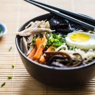 Zupa Ramen w miseczce z jajkiem, makaronem, marchewką, mięsem, grzybami i glonami. Na miseczce leżą pałeczki
