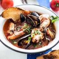 Zupa z owoców morza z krewetkami i mulami. Ozdobiona posiekaną natką pietruszki i przypieczoną grzanką z bagietki.