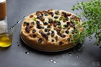 Focaccia z suszonymi pomidorami, oliwą i tymiankiem. Całość na czarnym blacie.
